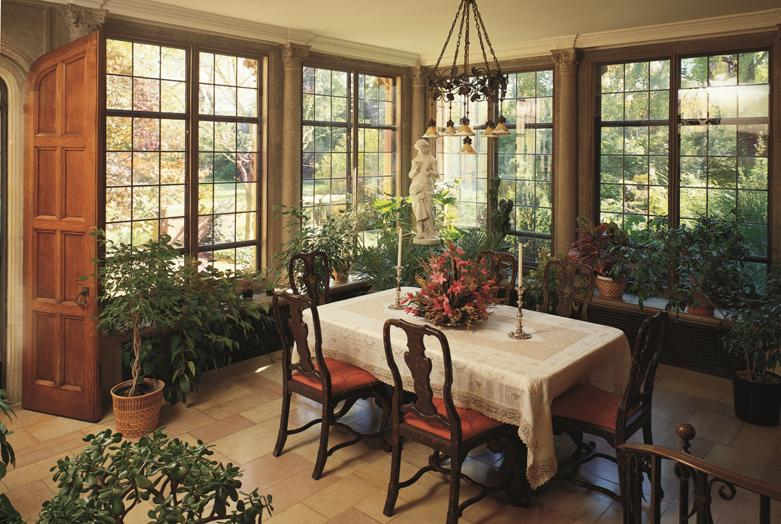 A rectangular table in a room with windows and plants