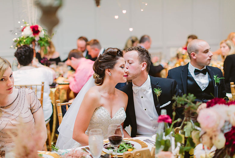 A groom kissing the bride at reception dinner