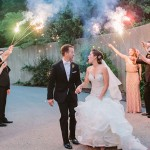 People holding sparklers over the heads of a bride and groom