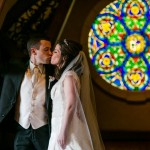 A bride and a groom kissing in front of a rose window