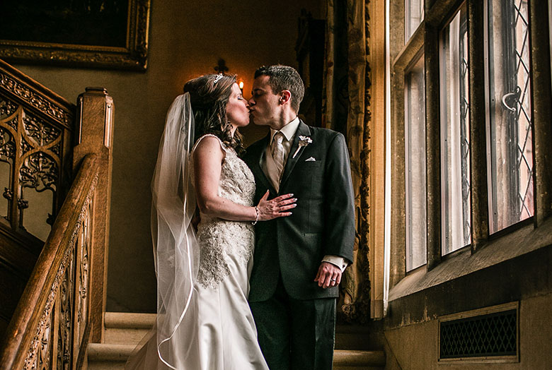 A bride and groom kissing on a stairwell