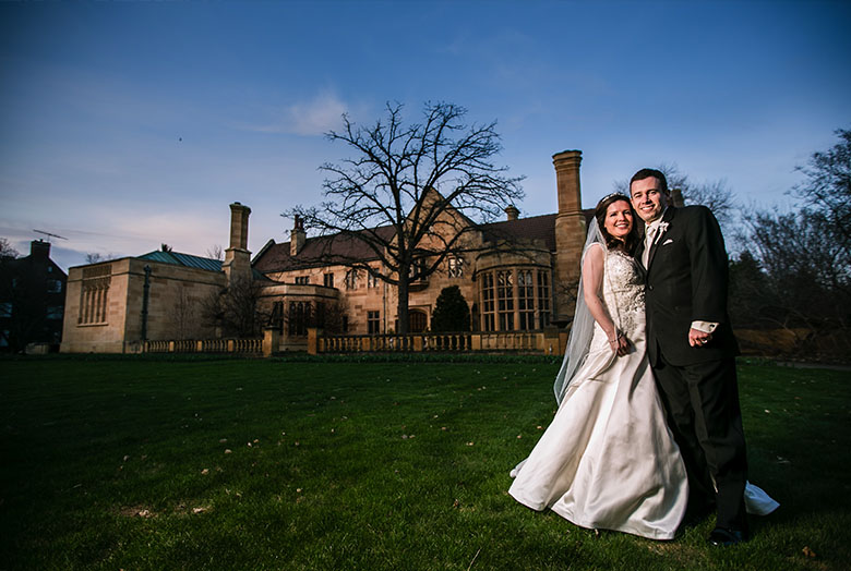A bride and groom in front of a mansion