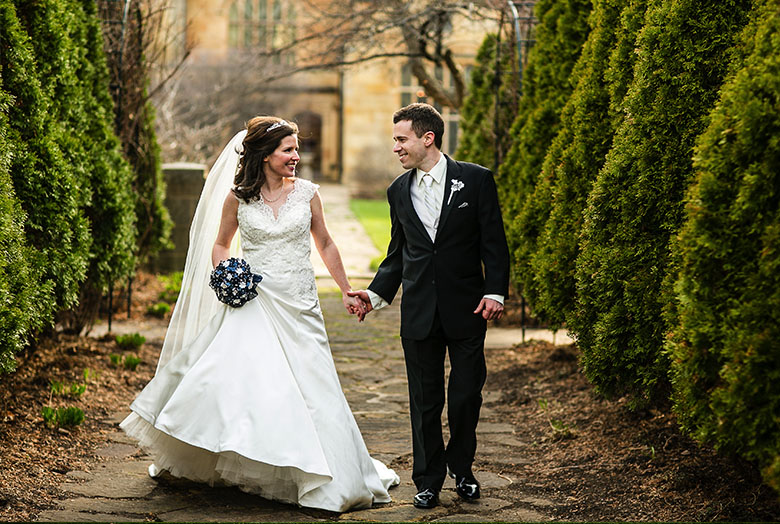 A bride and groom walking by evergreens