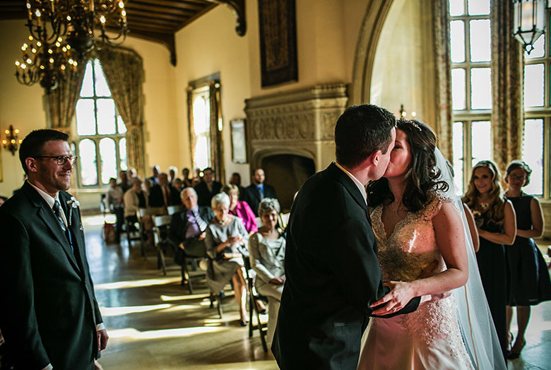 A groom kissing a bride during a wedding