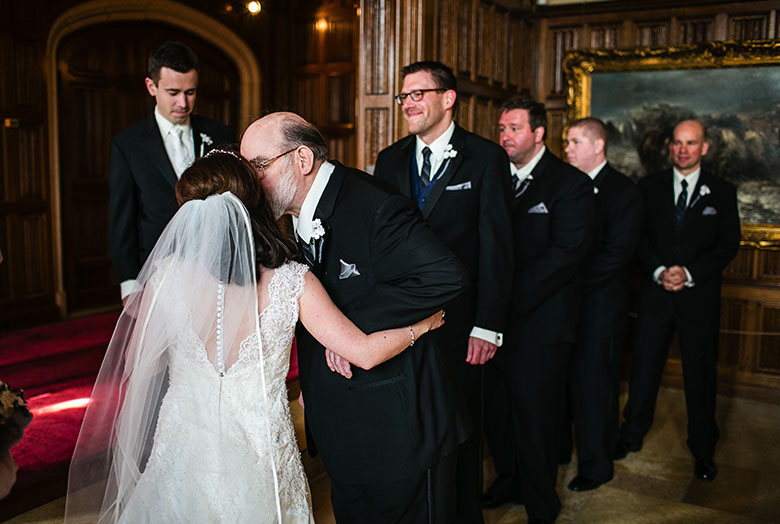 A man kissing the bride on the cheek