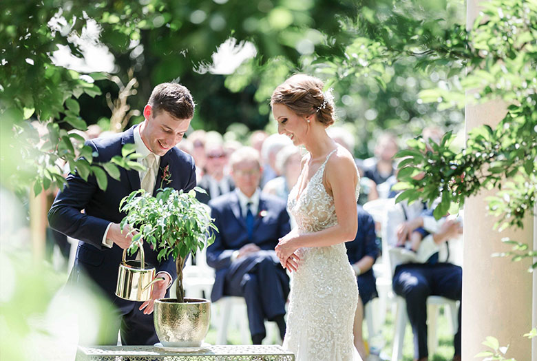 A bride and a groom planting a tree during a wedding ceremony