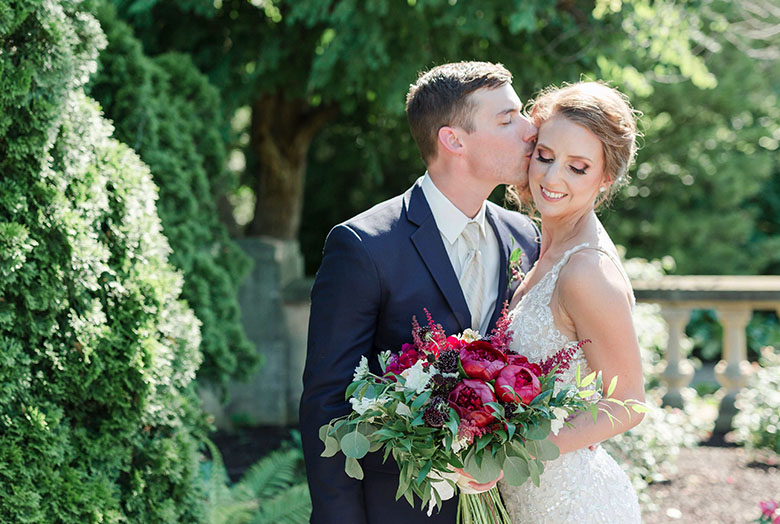 A groom kissing a bride on the cheek