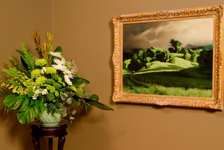 Image of a green floral arrangement next to a painting