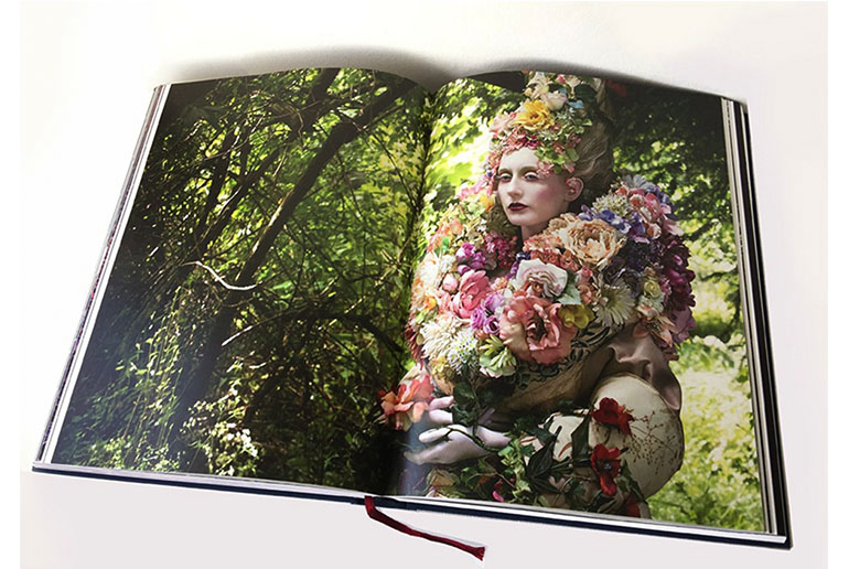 An open book with an image of woman covered in flowers