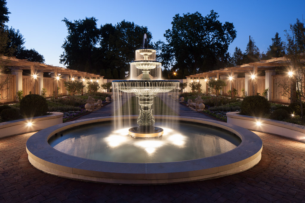 Soft lighting on a large fountain in a garden
