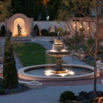 A garden with a center fountain illuminated at night