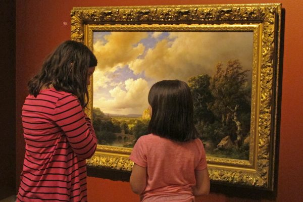 A woman and a girl in front of a painting of clouds