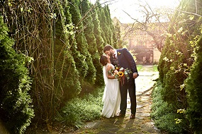A bride and a groom kissing in a garden