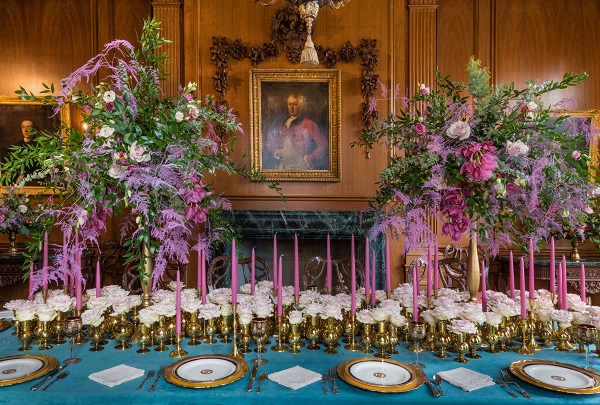 Two elaborate floral displays on a grand table in a mansion