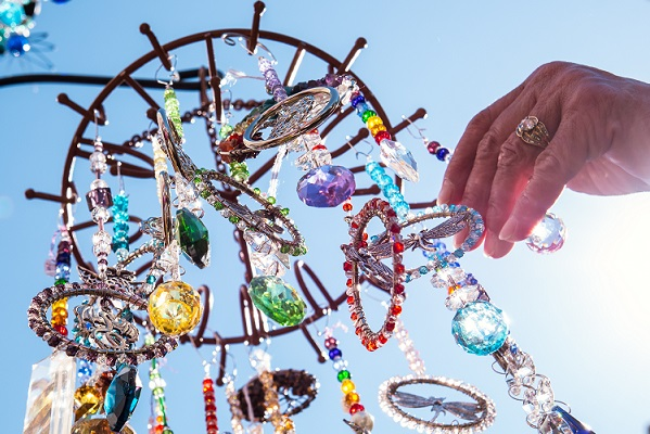 A hand touching beads on a colorful hanging mobile