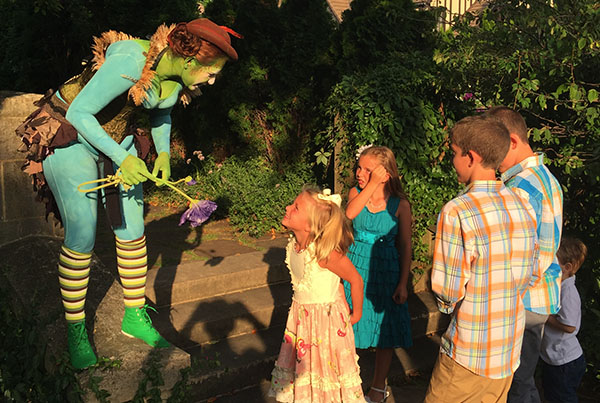 Children talking to a woman dressed as a garden fairy
