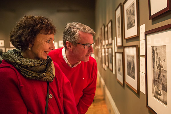 A man and a woman looking at artwork on the wall