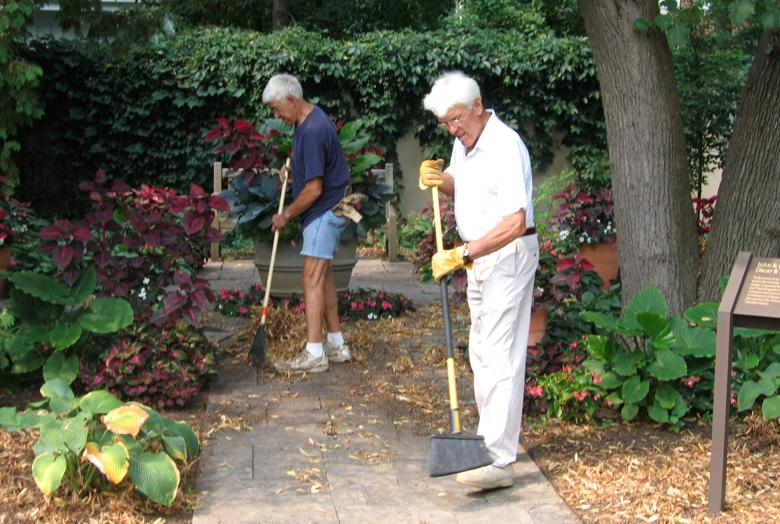 Two men brushing mulch by a garden