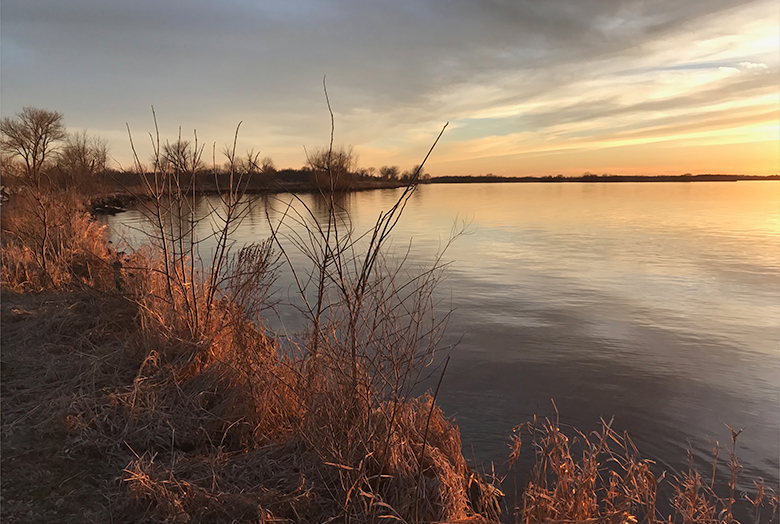 Photo of a sunset on water in late fall