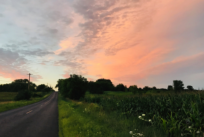 Photo of road running into the horizon at sunset