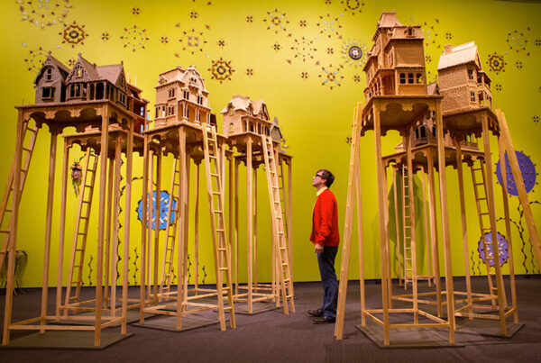 Art gallery with yellow walls and sculptures of houses on stilts