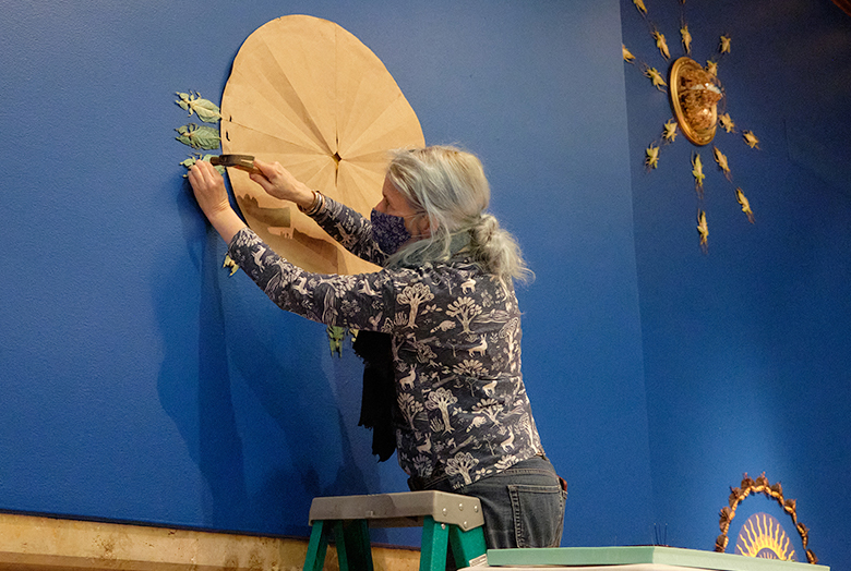 Arts hammers pin through insect onto blue gallery walls
